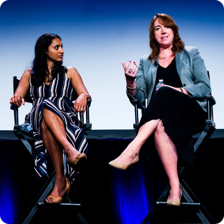 Two women in chairs on a stage. One listens while the other addresses the audience.