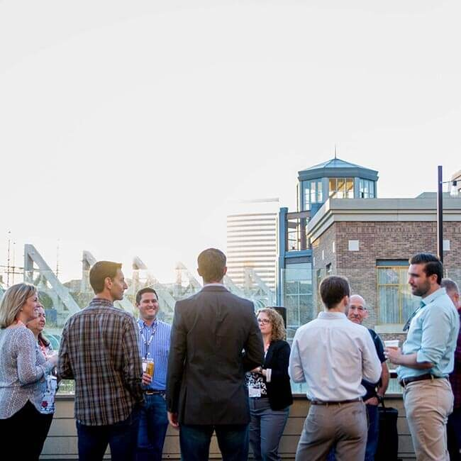 A group of men and women socializing outdoors at a Seismic conference, with a city view in the background